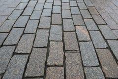 Άποψη προοπτικής σχετικά με οδικό στενό επάνω πετρών Πεζοδρόμιο του γρανίτη Καφετί τετραγωνικό πεζοδρόμιο κυβόλινθων Χλεύη επάνω  στοκ φωτογραφία