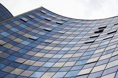 Άποψη προοπτικής της σύγχρονης πρόσοψης οικοδόμησης γυαλιού με τις αντανακλάσεις σύννεφων στα παράθυρα Στοκ Εικόνες
