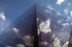 Άποψη προοπτικής της σύγχρονης πρόσοψης οικοδόμησης με τις αντανακλάσεις σύννεφων στα παράθυρα Στοκ Εικόνα