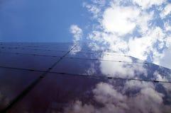 Άποψη προοπτικής της σύγχρονης πρόσοψης οικοδόμησης με τις αντανακλάσεις σύννεφων στα παράθυρα Στοκ Εικόνες