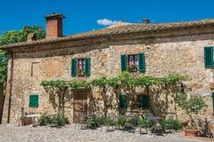 Άποψη προσόψεων ενός παλαιού σπιτιού με τα αναρριχητικά φυτά στο χωριουδάκι Monteriggioni στοκ εικόνα