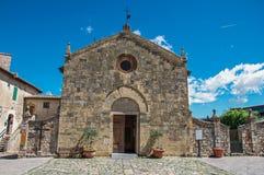 Άποψη προσόψεων μιας παλαιάς εκκλησίας σε μια ηλιόλουστη ημέρα στο χωριουδάκι Monteriggioni στοκ φωτογραφία με δικαίωμα ελεύθερης χρήσης