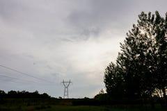 Άποψη σκιαγραφιών σχετικά με τη γραμμή ηλεκτρικής δύναμης, το δέντρο και το νεφελώδη ουρανό στοκ φωτογραφία