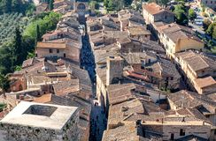 Άποψη στεγών σχετικά με τη εικονική παράσταση πόλης της Τοσκάνης Δημαρχεία SAN Gimignano και στενές οδοί με το πλήθος των τουριστ στοκ φωτογραφία