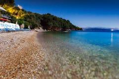 Άποψη στην παραλία Glyfa με τον τουρίστα στις καρέκλες και την κολύμβηση σαλονιών Στοκ εικόνα με δικαίωμα ελεύθερης χρήσης