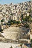 Άποψη στο αρχαίο ρωμαϊκό θέατρο με τα κτήρια κατοικήσιμης περιοχής στο υπόβαθρο στο Αμμάν, Ιορδανία Στοκ Εικόνες