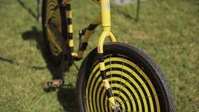 Άποψη στο μαύρο και κίτρινο δημιουργικό ποδήλατο που μένει στην πράσινη χλόη Θερινό φεστιβάλ ημέρα ηλιόλουστη απόθεμα βίντεο
