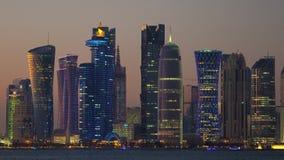 Άποψη στο σούρουπο πέρα από το νερό φωτισμένος κεντρικός, Doha απόθεμα βίντεο