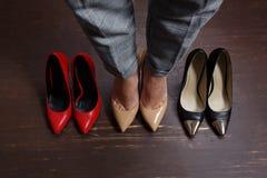 Άποψη συγκομιδών άνωθεν σε τρία ζευγάρια της γυναίκας, του κοκκίνου παπουτσιών, του Μαύρου και του μπλε Γυναίκα που στέκεται στα  στοκ εικόνα με δικαίωμα ελεύθερης χρήσης