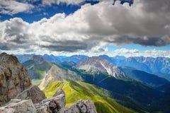 Άποψη Συνόδων Κορυφής της κύριας κορυφογραμμής Άλπεων Carnic κάτω από τα χνουδωτά άσπρα σύννεφα στοκ φωτογραφία με δικαίωμα ελεύθερης χρήσης