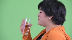 Άποψη σχεδιαγράμματος κινηματογραφήσεων σε πρώτο πλάνο του ευτυχούς νέου υπέρβαρου ασιατικού πόσιμου νερού γυναικών έτοιμου για τ απόθεμα βίντεο