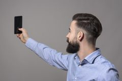Άποψη σχεδιαγράμματος του νέου σύγχρονου όμορφου γενειοφόρου επιχειρησιακού ατόμου που παίρνει selfie τη φωτογραφία με το smartph στοκ εικόνες
