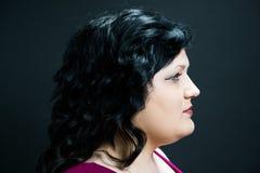 Άποψη σχεδιαγράμματος του σοβαρού νέου θηλυκού προτύπου με τα μπλε μάτια, τη σκοτεινή τρίχα, το δίκαιο δέρμα και τα κόκκινα χείλι στοκ φωτογραφία