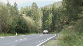 Άποψη σχετικά με έναν όμορφο δρόμο βουνών στα αυστριακά όρη στα οποία ένα motorbikeer και ένα αυτοκίνητο οδηγούν, άποψη των βουνώ φιλμ μικρού μήκους