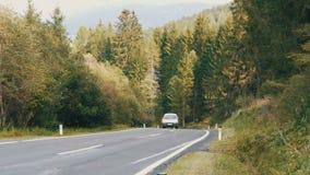 Άποψη σχετικά με έναν όμορφο δρόμο βουνών στα αυστριακά όρη στα οποία ένα motorbikeer και ένα αυτοκίνητο οδηγούν, άποψη των βουνώ απόθεμα βίντεο