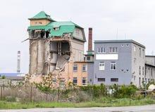 Άποψη σχετικά με ένα μερικώς καταρρεσμένο βιομηχανικό κτήριο τούβλου με την πράσινη στέγη μετάλλων και τον ελαφρύ ουρανό ανωτέρω  στοκ φωτογραφία με δικαίωμα ελεύθερης χρήσης
