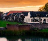 Άποψη σχετικά με μερικά σύγχρονα σπίτια με το νερό και τη χλόη στο ηλιοβασίλεμα στην πόλη Leerdam οι Κάτω Χώρες, χαρακτηριστική ο στοκ εικόνα με δικαίωμα ελεύθερης χρήσης
