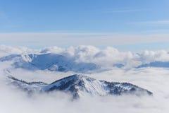 Άποψη σχετικά με τα βουνά και το μπλε ουρανό επάνω από τα σύννεφα Στοκ Εικόνες