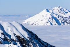 Άποψη σχετικά με τα βουνά και το μπλε ουρανό επάνω από τα σύννεφα Στοκ εικόνα με δικαίωμα ελεύθερης χρήσης