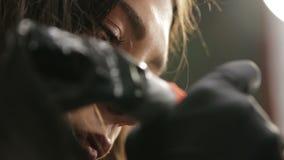 Άποψη σχετικά με τα μάτια και το πρόσωπο του όμορφου θηλυκού κυρίου δερματοστιξιών κατά τη διάρκεια της εργασίας φιλμ μικρού μήκους
