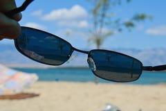 Άποψη σχετικά με την ηλιόλουστη παραλία μέσω των διοπτρικών γυαλιών ηλίου με το UV φίλτρο 400 στοκ εικόνες με δικαίωμα ελεύθερης χρήσης