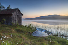 Άποψη σχετικά με την ομιχλώδη λίμνη με τις βάρκες στην ακτή Στοκ φωτογραφία με δικαίωμα ελεύθερης χρήσης