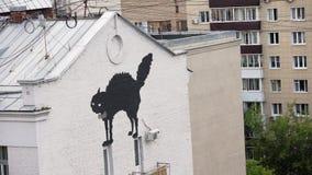 Άποψη σχετικά με την πρόσοψη του μεγάλου κτηρίου με την εικόνα μαύρης γάτας και δύο μπαλκονιών απόθεμα βίντεο