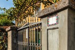 Άποψη σχετικά με τις πύλες εξοχικών σπιτιών με το κιγκλίδωμα επεξεργασμένος-σιδήρου Στοκ Φωτογραφία