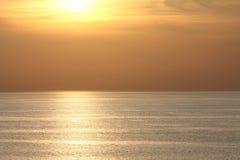 Άποψη σχετικά με τον ήλιο επάνω από τον ωκεανό στο πορτοκαλί ηλιοβασίλεμα με την αντανάκλαση σύστασης στο νερό Στοκ Εικόνες