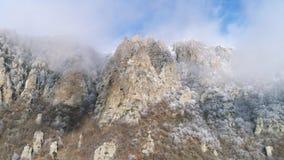 Άποψη σχετικά με τους μεγαλοπρεπείς απότομους βράχους βουνών στα γκρίζα σύννεφα ενάντια στο μπλε ουρανό, που εισβάλλεται από τα π φιλμ μικρού μήκους