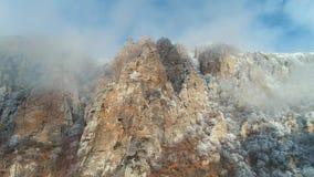 Άποψη σχετικά με τους μεγαλοπρεπείς απότομους βράχους βουνών στα γκρίζα σύννεφα ενάντια στο μπλε ουρανό, που εισβάλλεται από τα π απόθεμα βίντεο