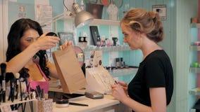 Άποψη σχεδιαγράμματος μιας αρκετά νέας γυναίκας που πληρώνει με μια πιστωτική κάρτα σε ένα κατάστημα απόθεμα βίντεο