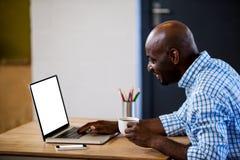 Άποψη σχεδιαγράμματος του επιχειρηματία που κρατά έναν καφέ και που δακτυλογραφεί στο lap-top του Στοκ φωτογραφία με δικαίωμα ελεύθερης χρήσης