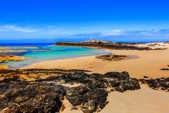 Άποψη της ακτής EL Cotillo, με τα φαράγγια και τα κύματα θάλασσάς του που συντρίβουν στους απότομους βράχους και την άσπρη παραλί στοκ φωτογραφίες