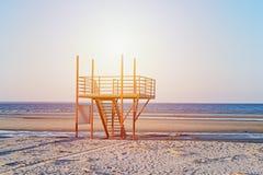 Άποψη της αμμώδους παραλίας ηλιοβασιλέματος με τον κόκκινο κενό σύγχρονο πύργο lifeguard στοκ φωτογραφίες