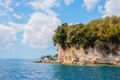 Άποψη της απομονωμένης δύσκολης ευθυγραμμισμένης απότομος βράχος ακτής με τα τυρκουάζ νερά στην ακτή της Ισπανίας, Ελλάδα την ηλι Στοκ Εικόνες