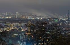 Άποψη της αρχαίας περιοχής Podil και της σύγχρονης περιοχής Obolon στο υπόβαθρο Πανόραμα πόλεων βραδιού Βράδυ χειμερινού Σαββατοκ Στοκ Φωτογραφία
