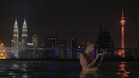 Άποψη της γυναίκας στην πισίνα στη στέγη ουρανοξυστών που κάνει selfie από την ταμπλέτα ενάντια στο τοπίο πόλεων νύχτας Κουάλα Λο φιλμ μικρού μήκους