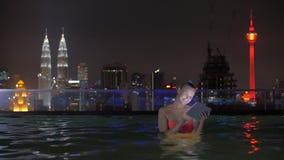 Άποψη της γυναίκας στην πισίνα στη στέγη ουρανοξυστών που χρησιμοποιεί την ταμπλέτα ενάντια στο τοπίο πόλεων νύχτας Κουάλα Λουμπο απόθεμα βίντεο