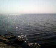 Άποψη της θάλασσας από την ακτή μια ηλιόλουστη ημέρα Ήρεμη θάλασσα με τους ελαφριούς κυματισμούς στην επιφάνεια του νερού και των στοκ εικόνα