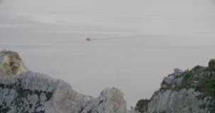 Άποψη της θάλασσας με μια βάρκα που πλέει στην απόσταση απόθεμα βίντεο