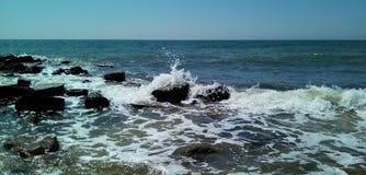 Άποψη της θάλασσας μια ηλιόλουστη ημέρα Στο πρώτο πλάνο είναι μικρά κύματα με τους παφλασμούς και τον άσπρο αφρό, υγρές σκοτεινές στοκ φωτογραφία με δικαίωμα ελεύθερης χρήσης