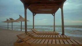 Άποψη της θάλασσας πρωινού πέρα από το gazebo παραλιών με τα ξύλινα sunbeds φιλμ μικρού μήκους