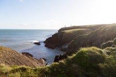 Άποψη της ιρλανδικής θάλασσας και των πράσινων χλοωδών παράκτιων απότομων βράχων Στοκ Φωτογραφία
