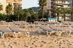 Άποψη της ισπανικής μεσογειακής παραλίας με τα sunbeds που προετοιμάζονται για τους τουρίστες στα ξημερώματα στοκ φωτογραφίες