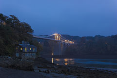 Άποψη της ιστορικής γέφυρας αναστολής Menai που φωτίζεται στη νύχτα, νησί Anglesey, Ουαλία Στοκ Φωτογραφία