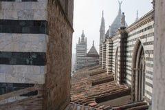 Άποψη της κεραμωμένης στέγης, των σχηματισμένων αψίδα παραθύρων και των μαρμάρινων αγαλμάτων στο Di Σιένα Duomo Μητροπολιτικός κα Στοκ Φωτογραφίες