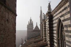 Άποψη της κεραμωμένης στέγης, των σχηματισμένων αψίδα παραθύρων και των μαρμάρινων αγαλμάτων στο Di Σιένα Duomo Μητροπολιτικός κα Στοκ Φωτογραφία