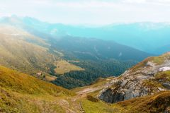 Άποψη της κοιλάδας με την κιτρινισμένα χλόη και τα δέντρα, που περιβάλλεται από τα υψηλά βουνά στην ομίχλη μια ημέρα φθινοπώρου στοκ εικόνες με δικαίωμα ελεύθερης χρήσης
