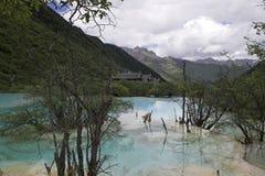 Άποψη της κοιλάδας με τις ζωηρόχρωμες λίμνες με τον αρχαίο ναό Huanglong στο υπόβαθρο στοκ εικόνα